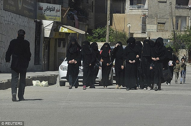 Brutal patrols: The duties of the all-woman jihadi group  include the strict enforcement of sharia law dress code as well as searching burka-clad women to ensure they are not enemy fighters in disguise