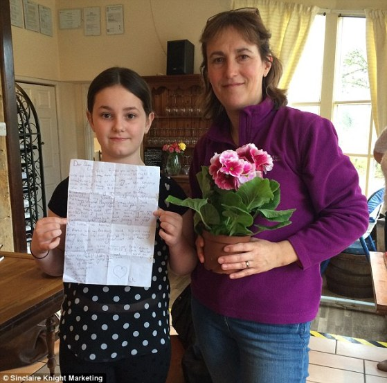 The touching note, which was found outside the Prince of Wales Pub on Ham Hill in Somerset, was written by Summer Lloyd, 10, (left) to her father on the fifth anniversary of his death. She planned to attach it to a balloon but dropped it. Summer gave a plant to the pub's landladyNicki Holroyd (right) after she returned it today