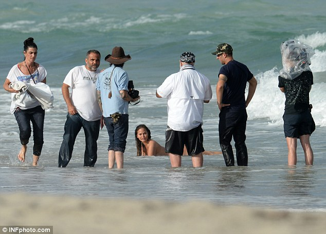 In the nude: She laid down in the surf, her slender curves on full show in the water, as the crew gathered around her