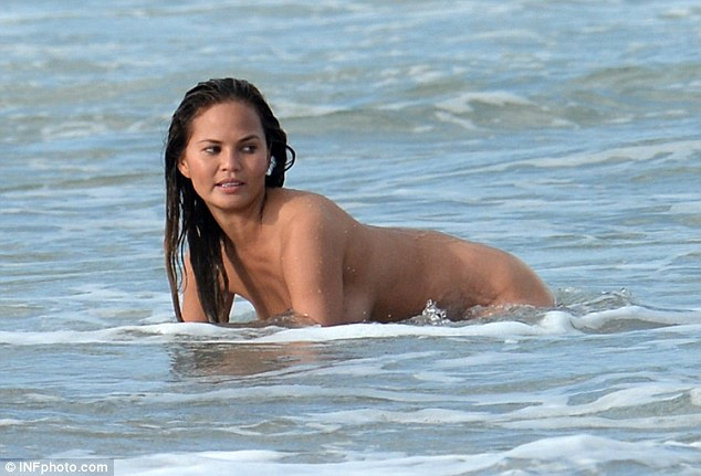 Topping up the tan: Chrissy made sure all of her body got some rays as she sat in the ocean