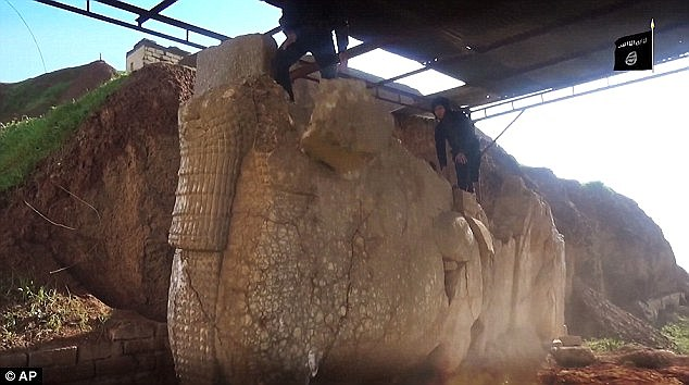 Historic loss: Large segments of the priceless winged-bull Assyrian protective deity are hurled to the ground as militants smash it to pieces
