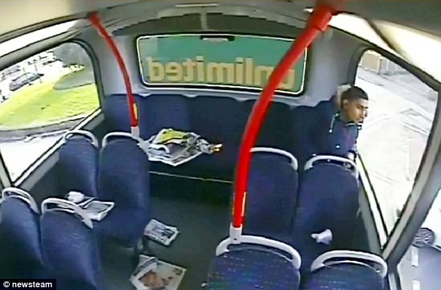 The youngster peers out of the window apparently unconcerned at the fire catching on the papers next to him