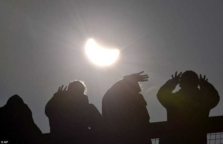 Lining up: Spectators at the Eden Project watch the eclipse with their special glasses but still have to shield their eyes because of the sharp sunlight
