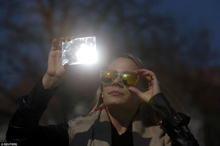 Lens: A woman in Budapest using a special glass lens to watch the eclipse