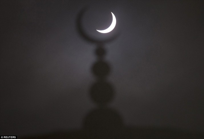 Framed: The partial solar eclipse seen above a mosque in Oxford topped with the Islamic crescent symbol