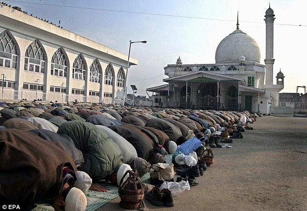There will be more Muslims than Christians in the world in less than sixty years, the Pew Research Center has claimed. Above, Kashmiri Muslims pray outside a mosque in Srinagar