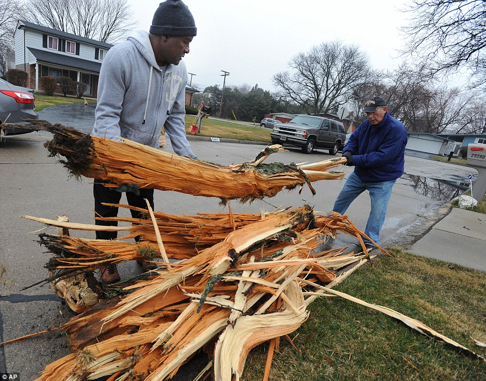 Neighbors Robert Frye, left, and Barry Winkler help clean up splintered tree parts that blasted into their yards after a storm passed the area in Southfield, Michigan,  on Thursday