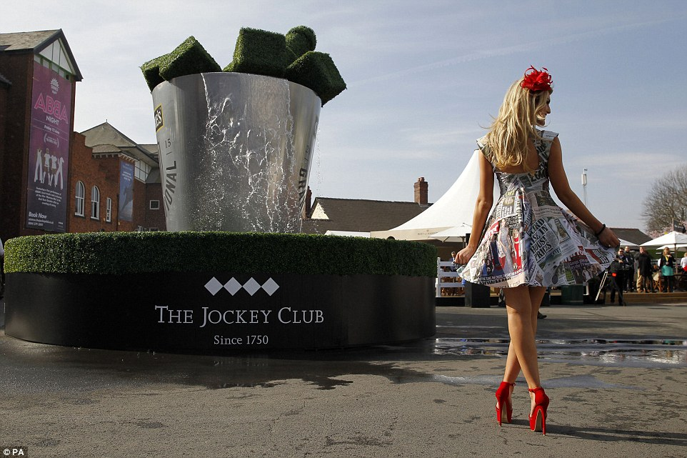 Sunshine: Racegoer Lydia Brown strikes a pose in front of the fountain that sits at the entrance of the Aintree racecourse