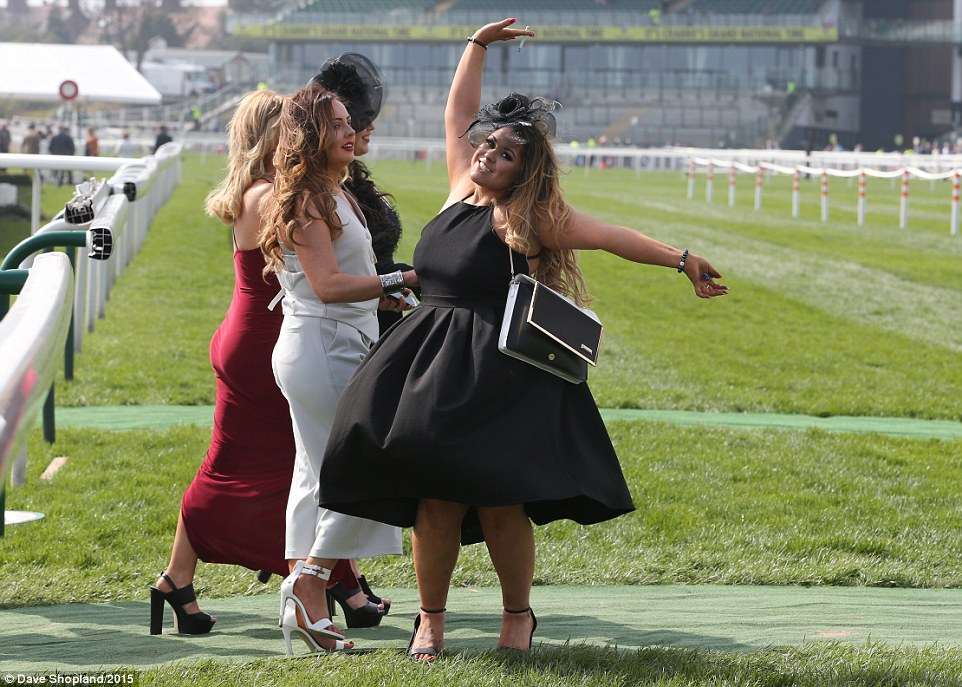 Dancing queen: A lady gives the cameras a twirl while crossing the racecourse in her high heels