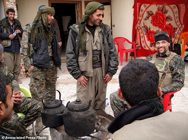 Jordan Matson, 28, far right, a former US Army soldier, takes a break with other fighters from the YPG in Sinjar, Iraq