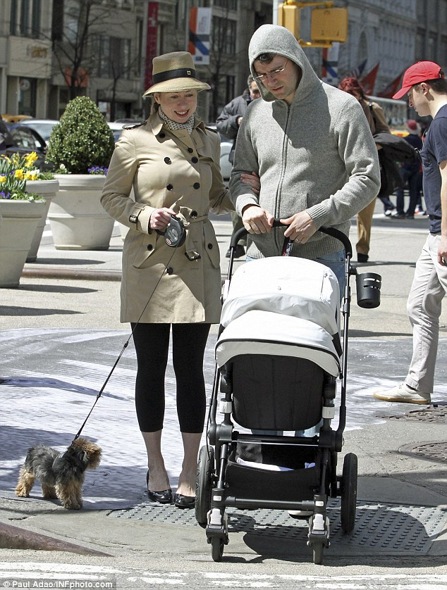 Happy family: Donning a beige sunhat, a matching coat and black leggings, 35-year-old Ms Clinton was captured beaming as she strolled beside Mr Mezvinsky, with one hand holding on to her spouse's arm