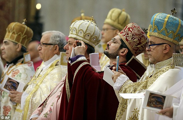 In memoriam: Prelates take pictures as Pope Francis during the mass in the Vatican today