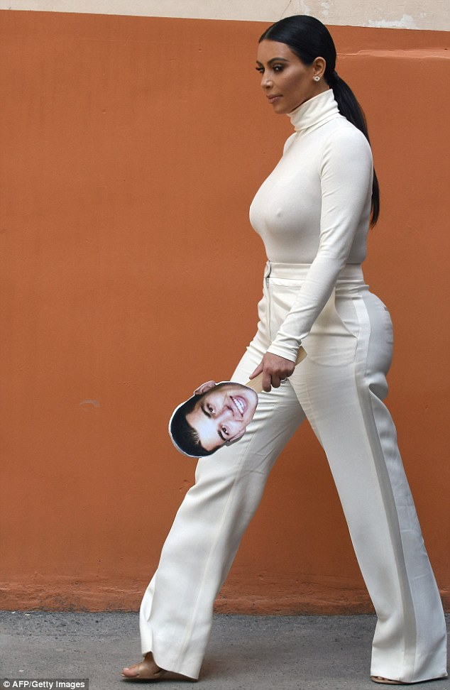Missing you: Kim Kardashian was eleant in an all-white outfit as she carried a cut-out of her younger brother Rob's face while touring through the city of Yerevan, Armenia on Sunday
