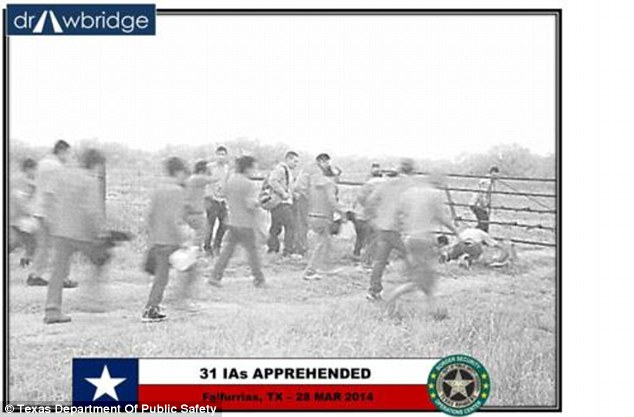 A group of suspected illegal immigrants crawl under a fence as they attempt to make their way into Texas