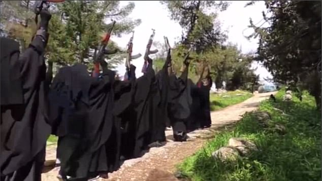 In the footage, a woman thought to be the former lead guitarist is seen leading the female militia as they march single-file along a dusty road, waving their AK-47s in the air