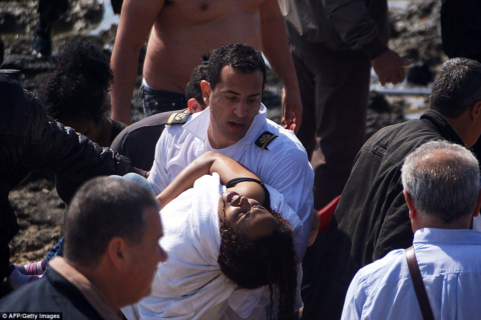 On dry land: A woman appears to collapse with exhaustion in her rescuers arms after being plucked from the Mediterranean Sea in Rhodes