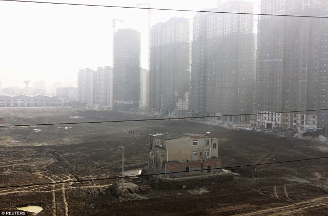 A nail house is seen surrounded by a ditch at a construction site for a new residential compound in Xiangyang, Hubei province