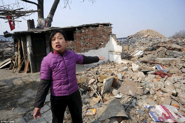 Cao Mingyun, daughter of 75-year-old Cao Wenxia, the owner of a nail house, talks to journalist in front of their house in Hefei, Anhui province