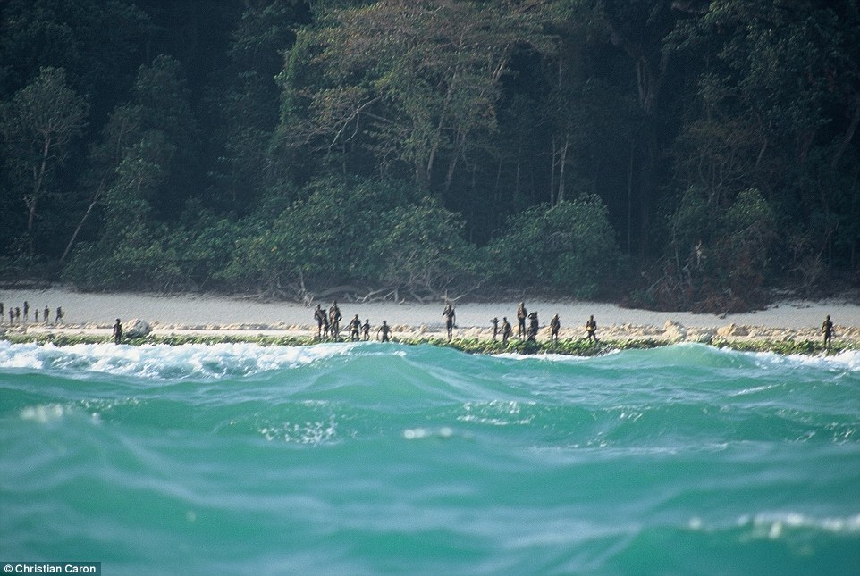 Sentinelese tribespeople, holding javelins, gather on the shore of North Sentinel Island, located in the Bay of Bengal
