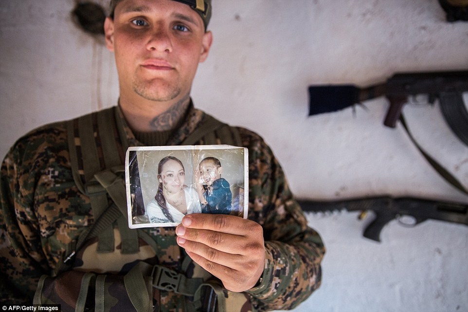 Remembering family:A 26-year old from the U.S., nick-named  Hewal Dilsad by Kurdish fighters, shows a picture of his wife and son