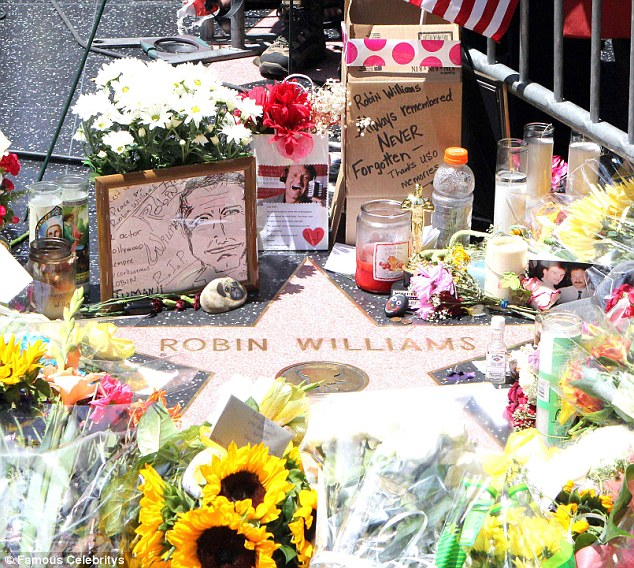 Tribute: Flowers and candles at the Oscar-winning actor's star on the Hollywood Walk of Fame. The day before he hanged himself, Williams stuffed his watch collection into a sock and took it to a friend for safekeeping