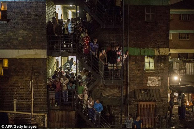 Raid: Zulu hostel dwellers on the staircase during a joint South African Police and army raid in Johannesburg yesterday. The raid was aimed at tackling gangs which have been hunting down and killing foreigners