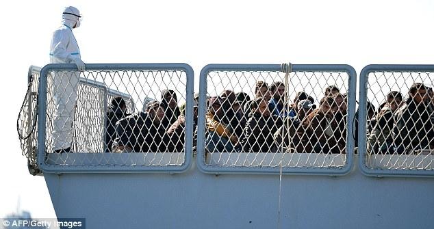 Un oficial de la Marina italiana se pone delante de inmigrantes rescatados a bordo del buque de la marina de guerra italiana Bettica a medida que llegan en el puerto siciliano de Augusta después de ser el grupo más reciente que ser rescatado desde el Mediterráneo