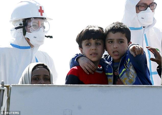 Aterrorizado: Niños abrazan a medida que llegan los inmigrantes en el puerto siciliano de Augusta con la marina italiana