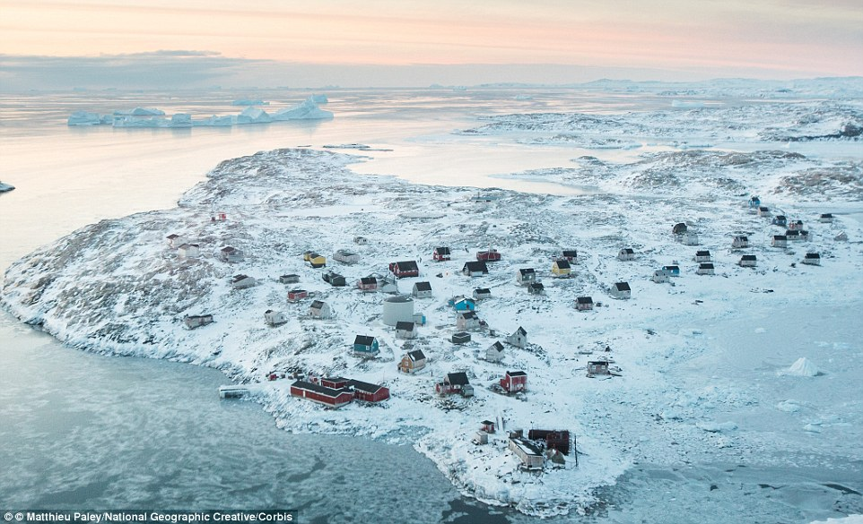 The remote east Greenland village of Isortoq includes a supermarket, the large red building (pictured front)