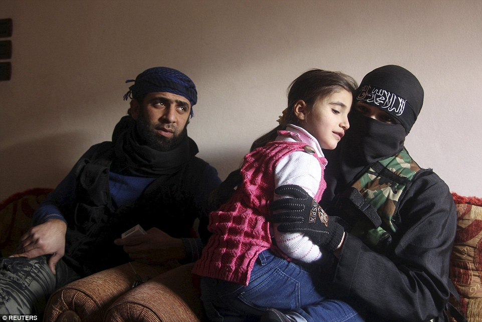 Tender touch: Um Jaafar, a woman fighter in the Free Syrian Army, sits with her husband Abu Jaafar, a Sawt al-Haq (Voice of Rights) battalion commander, and her daughter Faten at their home in Aleppo