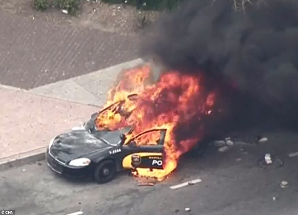 Fire fight: A Baltimore police cruiser burns after being set alight on Monday following the outbreak of riots in the troubled city