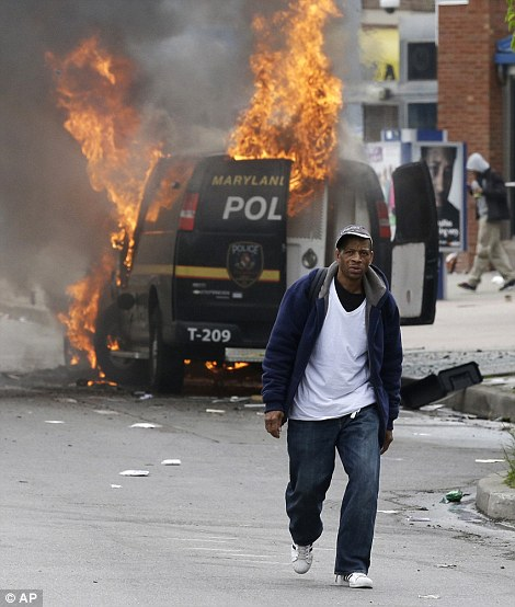 A man walks past a burning police vehicle during unrest in Baltimore. A helicopter circled overhead as groups of roving youths moved through the city. Television footage showed one group of demonstrators pile on top of and ride a car as it drove in the street