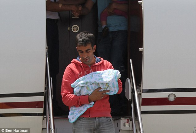 Wrapped in a blanket: The parents who were pictured returning to Sde Dov Airport on Monday had traveled abroad before Saturday's disaster to collect their children. Four surrogate mothers are also being rescued