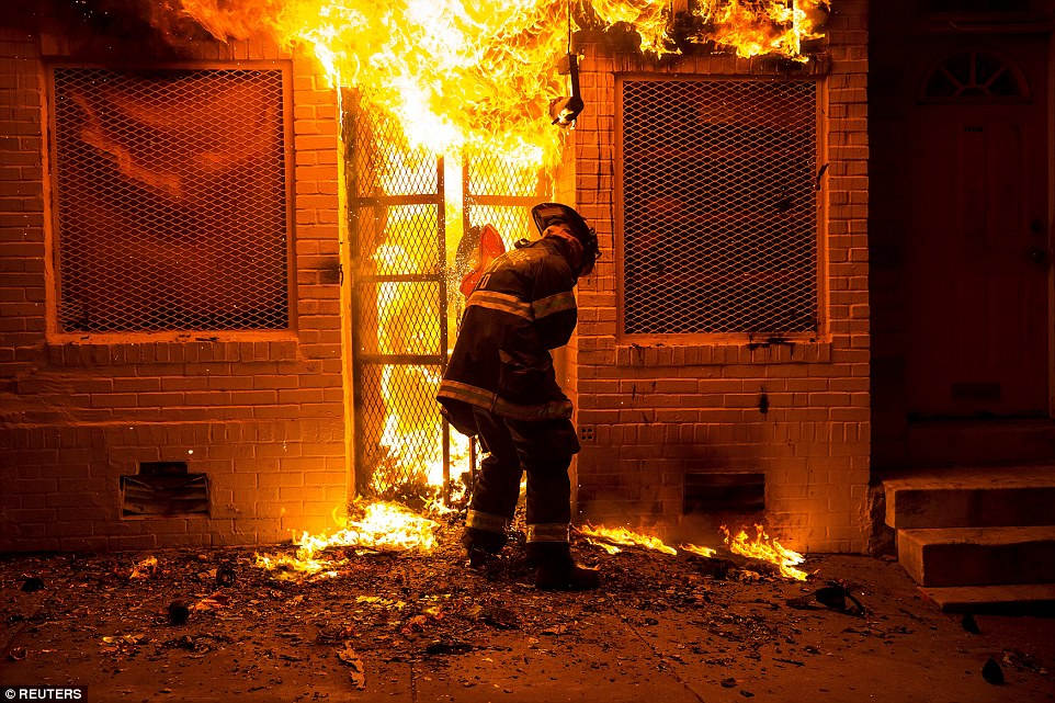 A firefighter uses a saw to open a metal gate while fighting a fire in a convenience store and residence during clashes in Baltimore