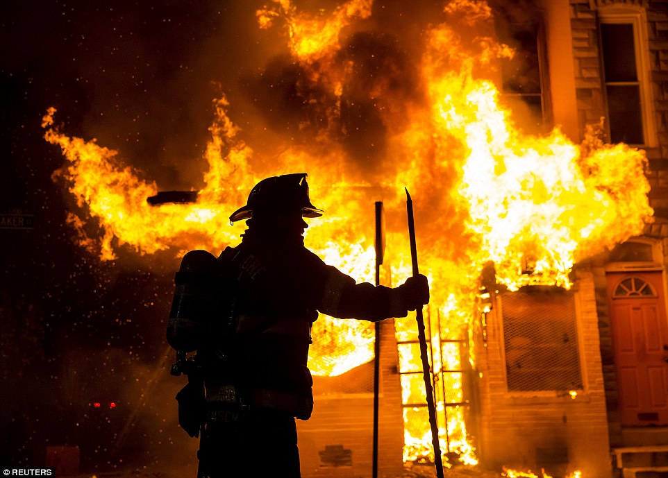 A Baltimore firefighter attacks a fire at a convenience store and residence during clashes after the funeral of Freddie Gray in Baltimore