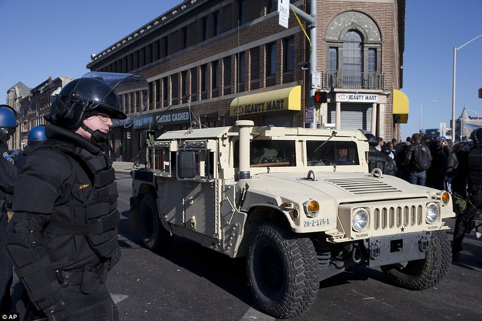 Protecting the streets: A National Guard vehicle drives by a Maryland State Trooper in the aftermath of the huge riots that broke out in Baltimore on Monday