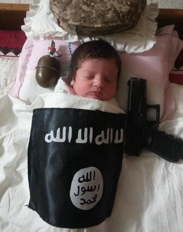 Chilling: A sleeping baby is placed next to a handgun and grenade and draped in a blanket with the sinister symbol of the Islamic State terror group