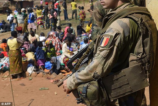 A French soldier taking part in 'Operation Sangaris' stands guard  at the Boali church as people sit on the floor
