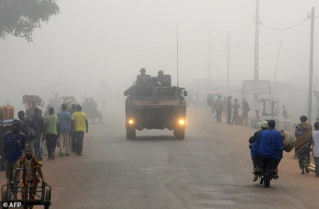 French soldiers patrol in a tank in Bangui amid dust as citizens go about their daily business