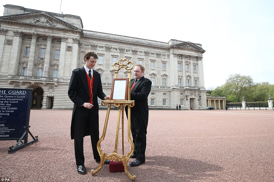 An easel is placed by two footmen in the forecourt of Buckingham Palace in London to announce the birth of a Royal baby girl