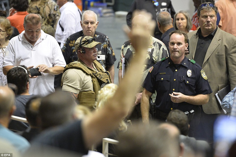 Members of the police and swat ask people from the audience if they heard or witnessed anything from the shooting