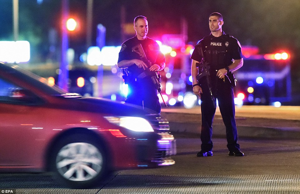 Two heavily-armed officers stand guard as police blocked off the street surrounding the scene in Garland, Texas