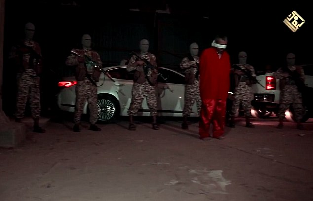 Sinister: A group of masked militants line up behind the prisoner, who is accused of spying for the Iraqi army