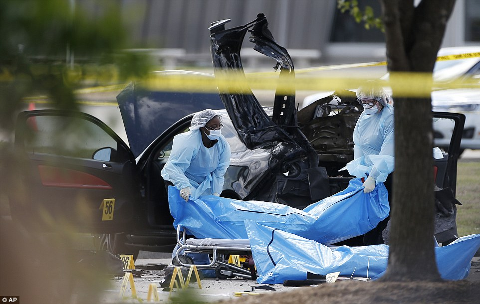 Taken away: Personnel remove the bodies of the two slain gunmen, who lived together in Phoenix, Arizona, on Monday