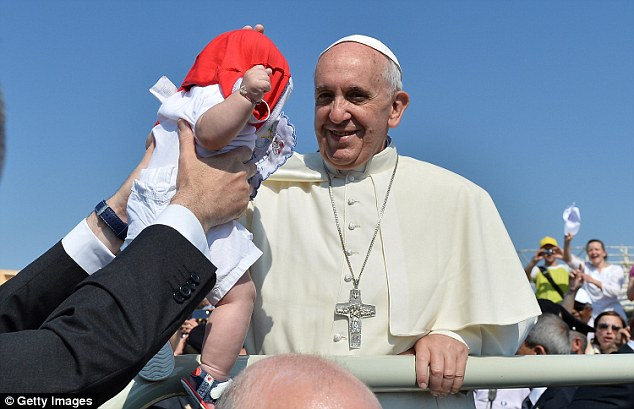 Pope Francis is handed a child to bless on his first official trip outside Rome since taking the Papacy
