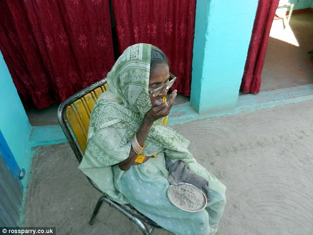 Mrs Devi sits in a corner outside a property in India on a yellow deckchair and licks her hand clean of sand