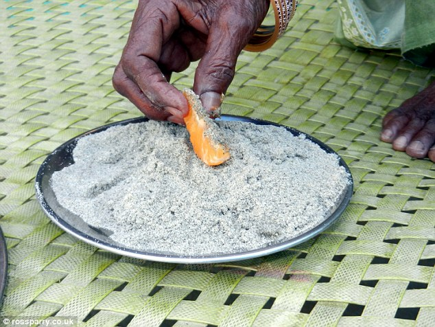 The elderly woman dips a piece of what appears to be orange in a plate of sand, which she believes keeps her healthy