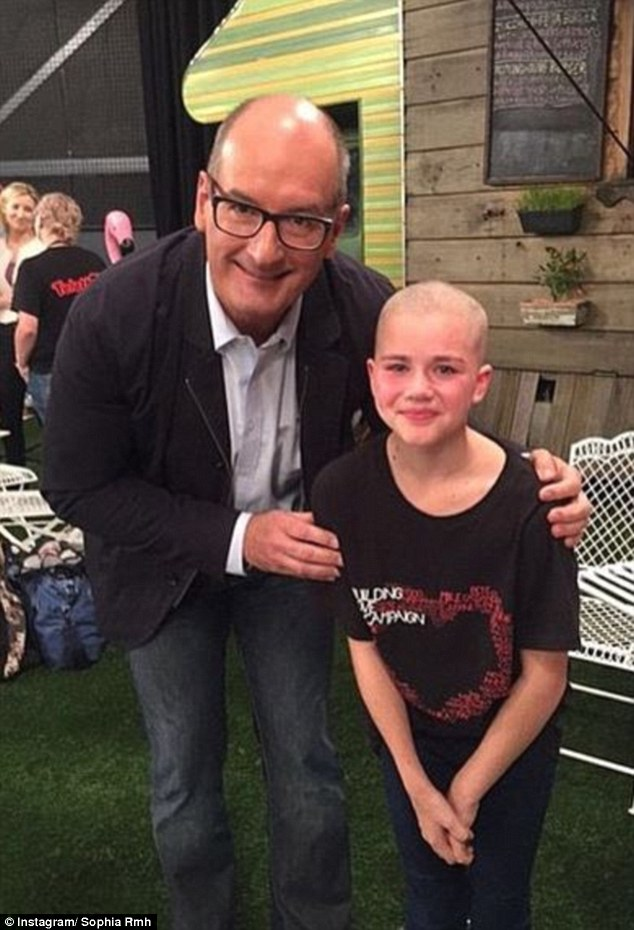 Channel Seven's Kochie gives her a cuddle after she shaved her hair at the telethon