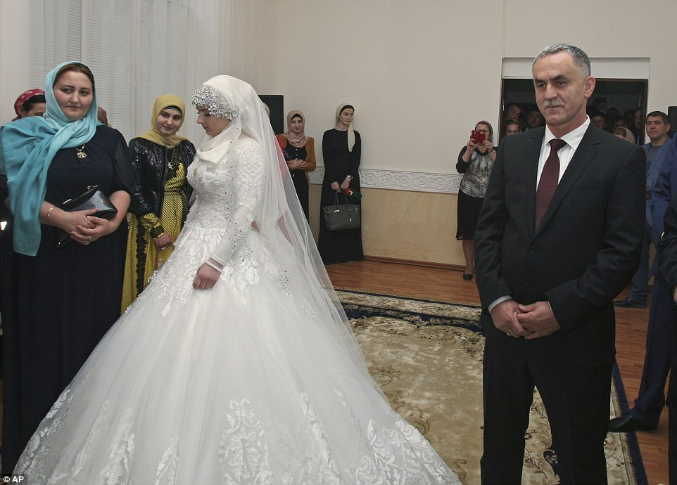 Close to tears: The teenager appears downtrodden as she stands feet away from her husband-to-be (right) at the registry office in Grozny