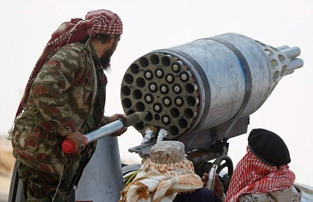 Deadly: Some images appear to show Libyan militia soldiers (pictured) loading missiles into a multiple rocket launcher